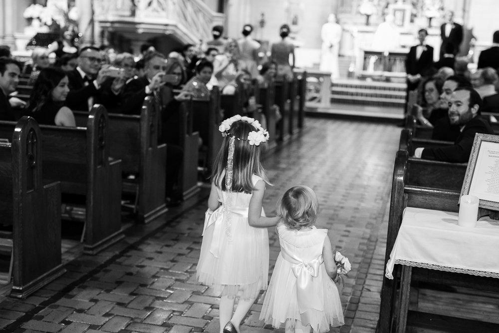 Flower girls walking down the aisle.