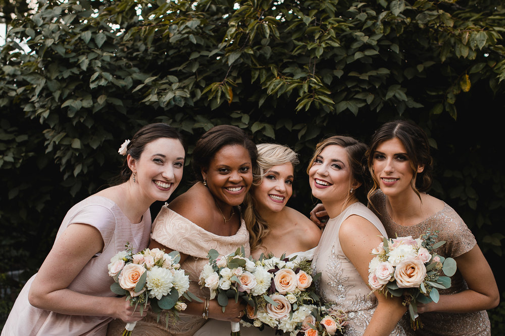 Bridesmaids grinning in Central Park, clustered around the bride.