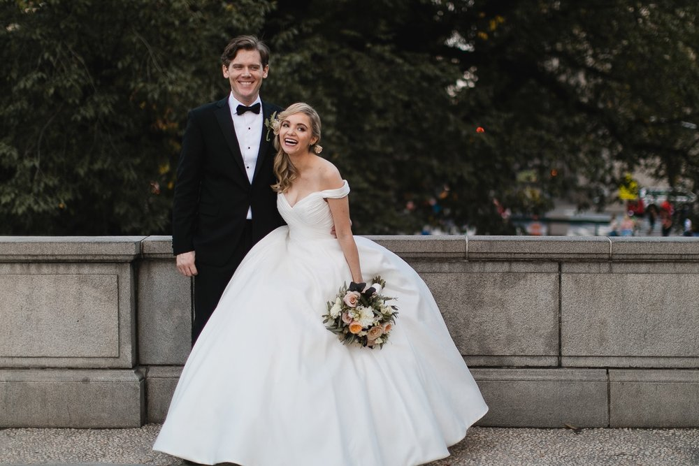 Bride and groom in Central Park giggling.