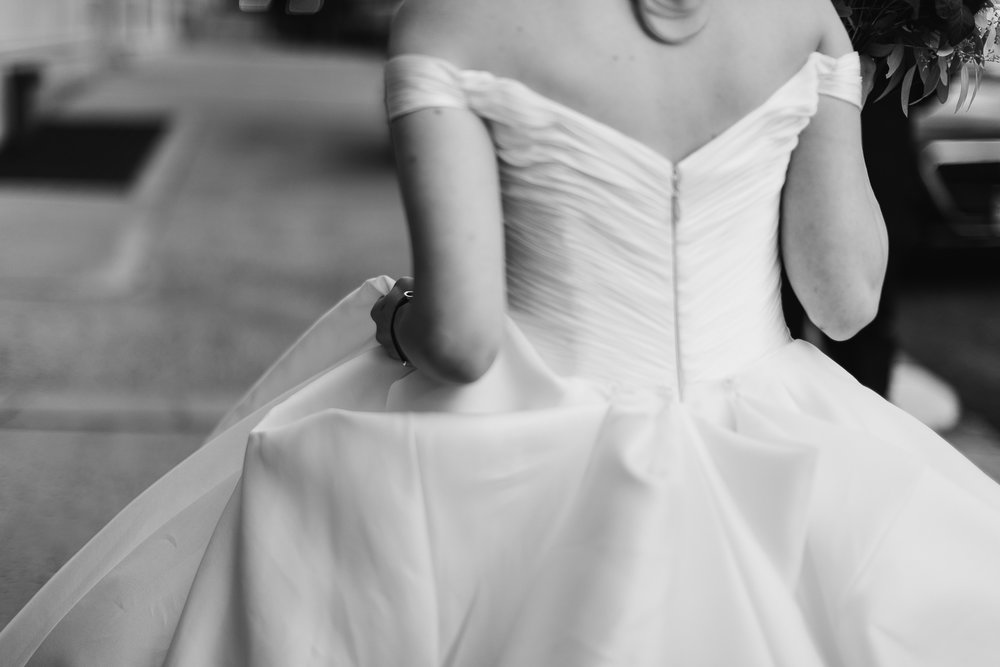 Black and white detail of the back of a bride's Anne Barge gown.