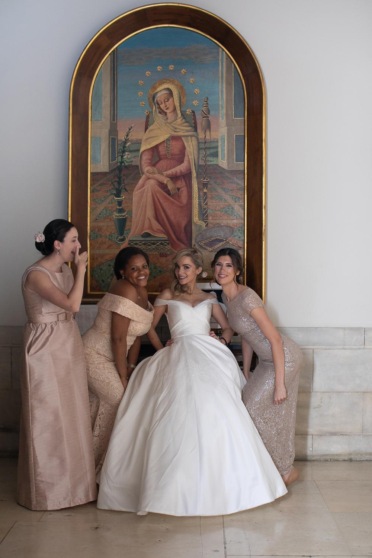 Bride posing with her bridesmaids waring blush pink dresses.
