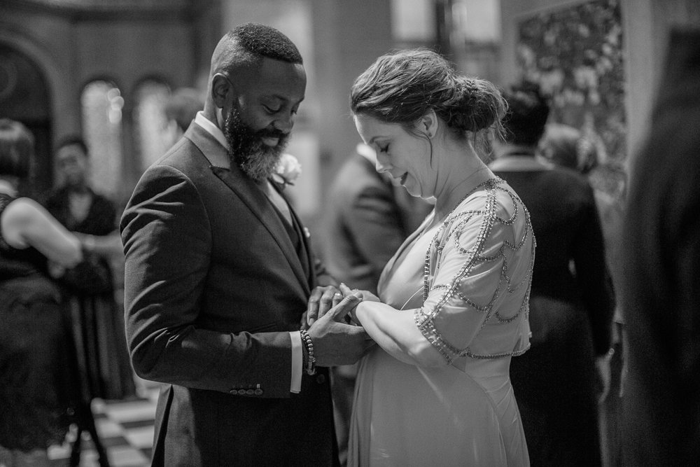Black and white portrait of a bride and groom holding hands at their intimate restaurant wedding in New York City. | Upper West Side Intimate Wedding | Kate & Sylvester's wedding in Manhattan.