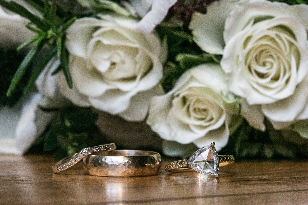 The wedding rings in front of white flowers. | Upper West Side Intimate Wedding | Kate & Sylvester's wedding in Manhattan.