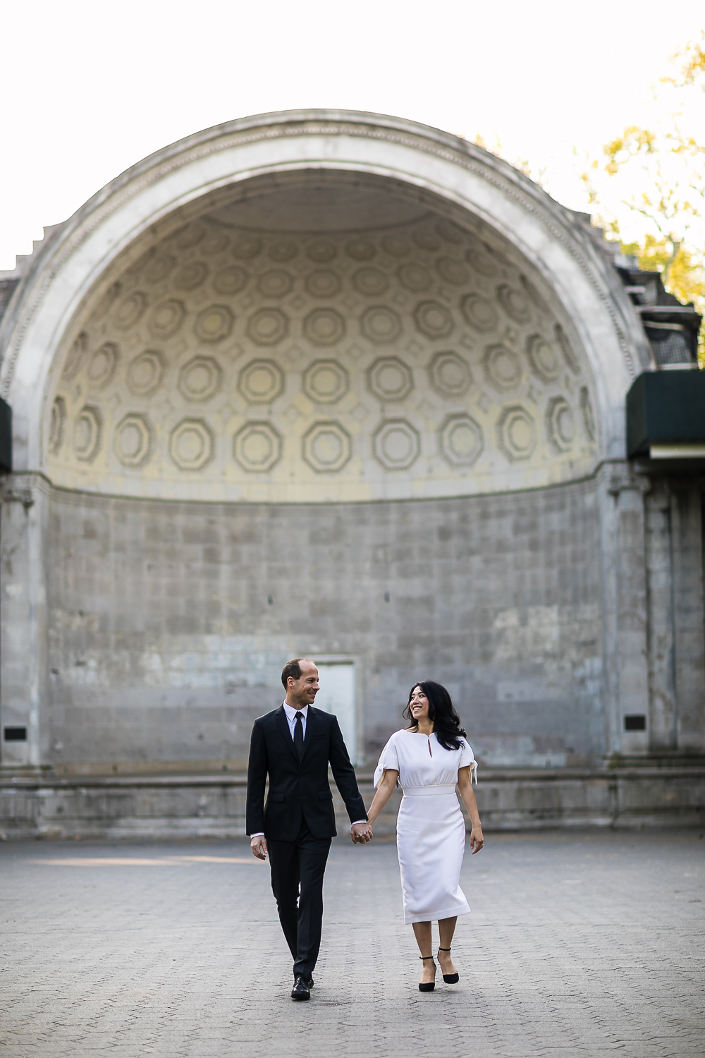 Bride and groom taking wedding photos at Naumburg Bandshell in Central Park. | Early Morning Sunrise Central Park Elopement in New York City.
