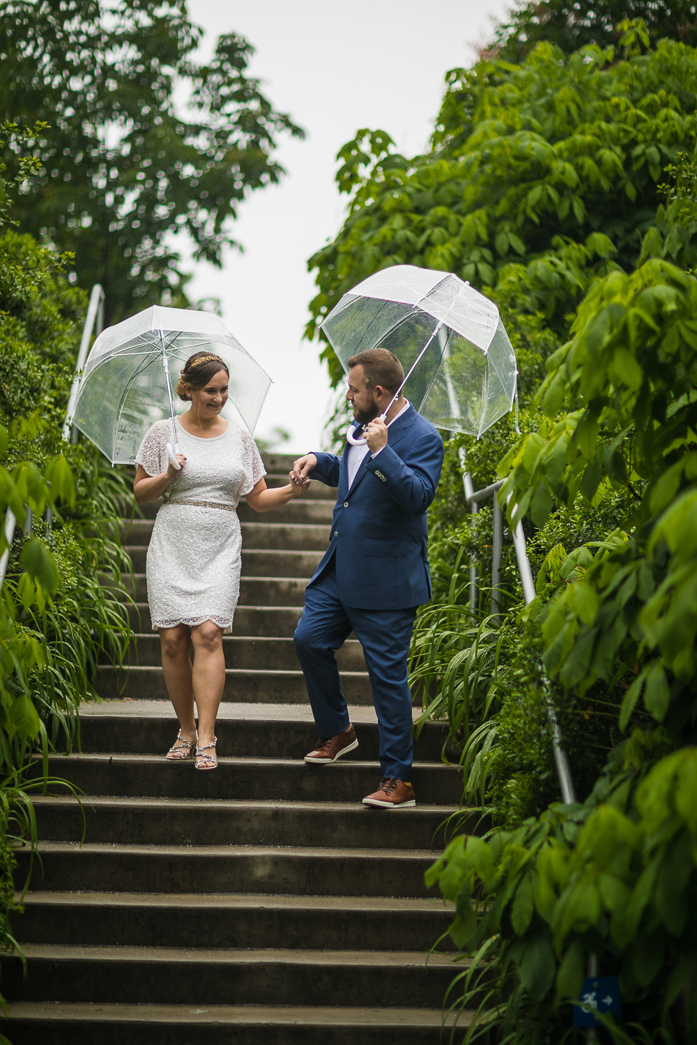 New York Bride in a short wedding dress and groom in a blue suit with clear plastic umbrellas in the rain. | Intimate Wedding at the Malthouse in Manhattan, New York City.
