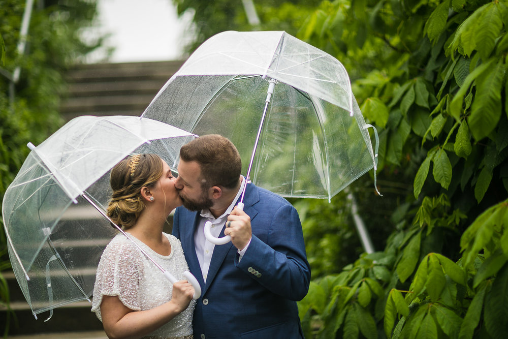 Bride and groom kissing in the rain. New York Bride in a short wedding dress and groom in a blue suit with clear plastic umbrellas in the rain. | Intimate Wedding at the Malthouse in Manhattan, New York City.