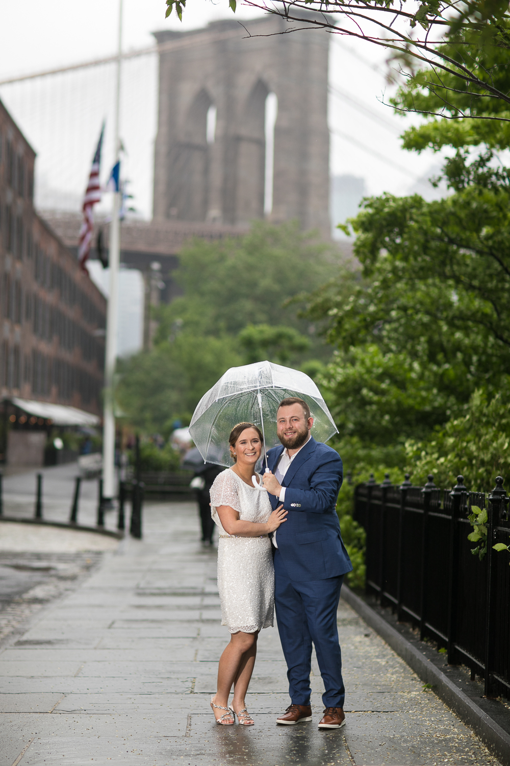 Wedding photos in front of the Brooklyn Bridge. New York Bride in a short wedding dress and groom in a blue suit with clear plastic umbrellas in the rain. | Intimate Wedding at the Malthouse in Manhattan, New York City.
