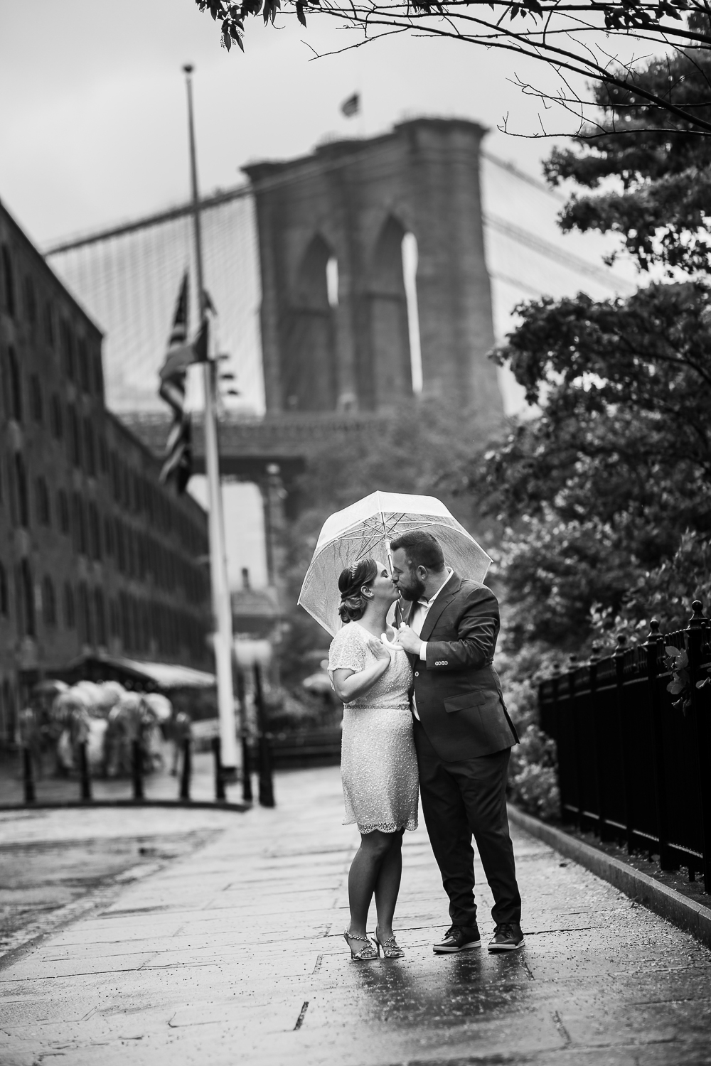 Black and white wedding photos in front of the Brooklyn Bridge. New York Bride in a short wedding dress and groom in a blue suit with clear plastic umbrellas kiss in the rain. | Intimate Wedding at the Malthouse in Manhattan, New York City.