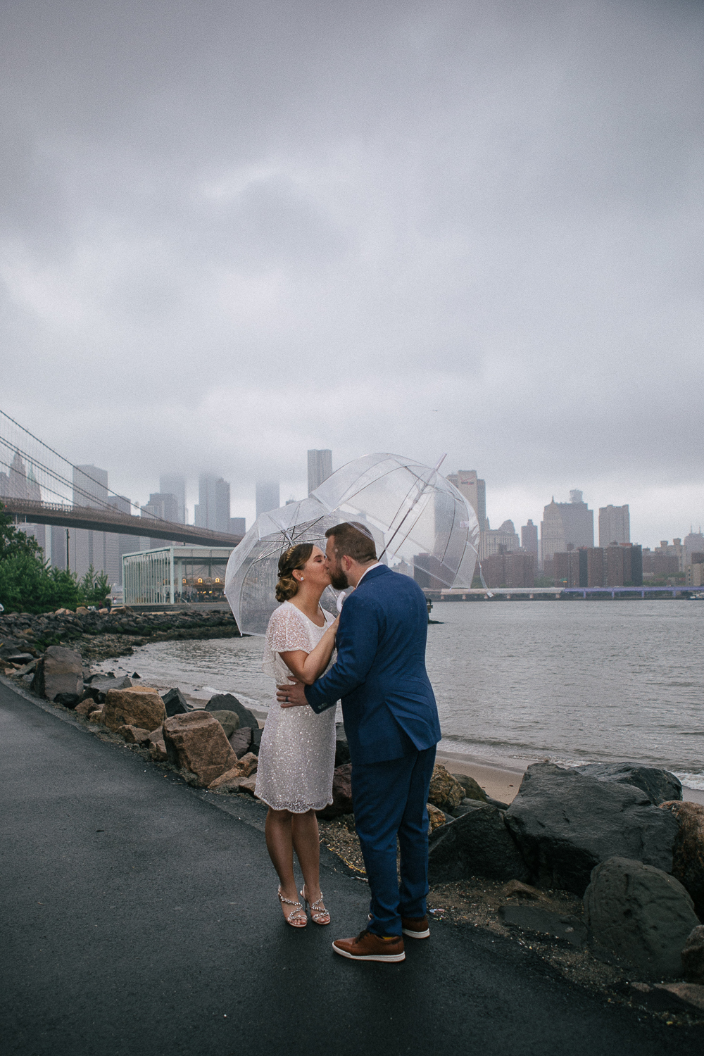 Wedding photos in front of the Brooklyn Bridge. New York Bride in a short wedding dress and groom in a blue suit with clear plastic umbrellas kiss in the rain. | Intimate Wedding at the Malthouse in Manhattan, New York City.
