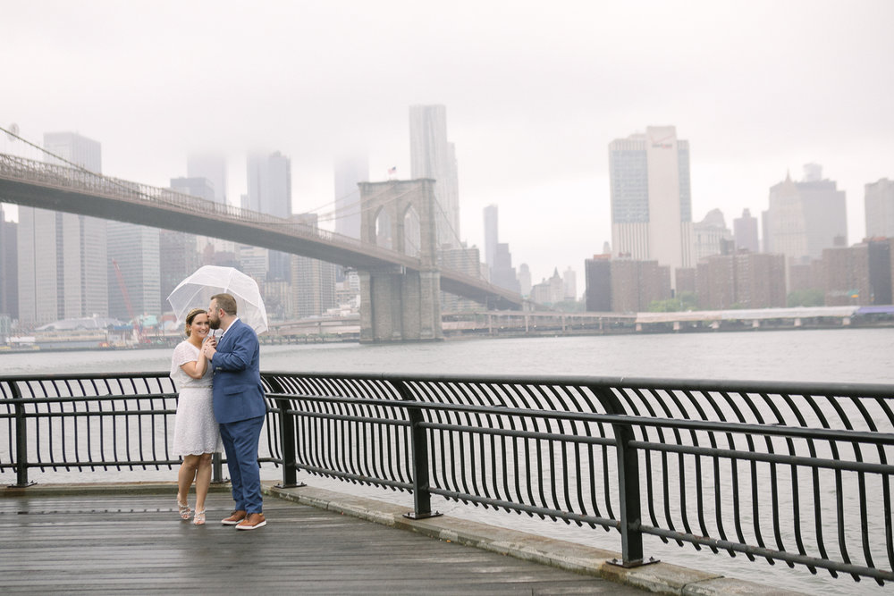 Wedding photos in front of the Brooklyn Bridge. New York Bride in a short wedding dress and groom in a blue suit pose with a clear plastic umbrella in front of the Brooklyn Bridge. | Intimate Wedding at the Malthouse in Manhattan, New York City.