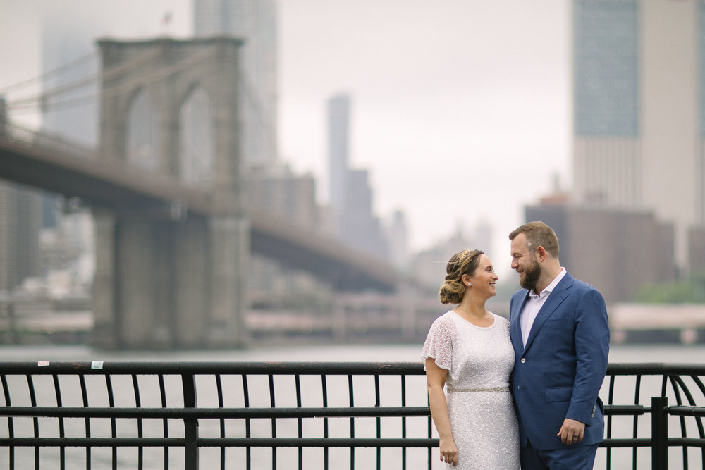 Brooklyn Bridge wedding portraits. New York Bride in a short wedding dress and groom in a blue suit pose in front of the Brooklyn Bridge. | Intimate Wedding at the Malthouse in Manhattan, New York City.