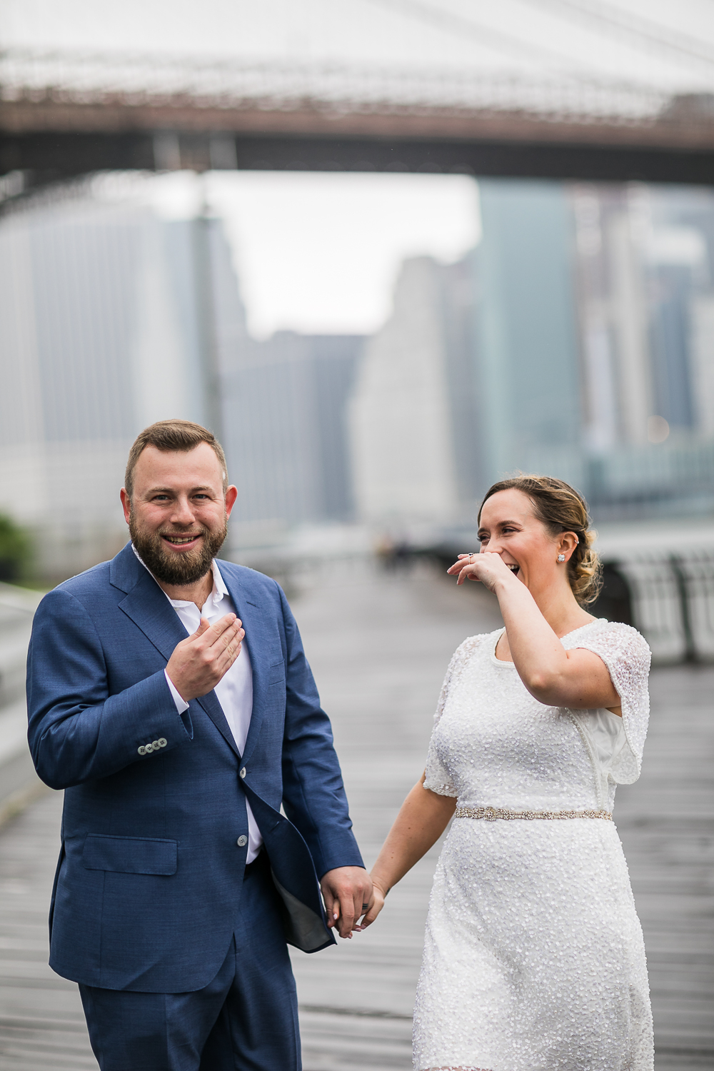 Bride and groom laughing. New York Bride in a short wedding dress and groom in a blue suit pose together for outdoor wedding photos in New York City. | Intimate Wedding at the Malthouse in Manhattan, New York City.
