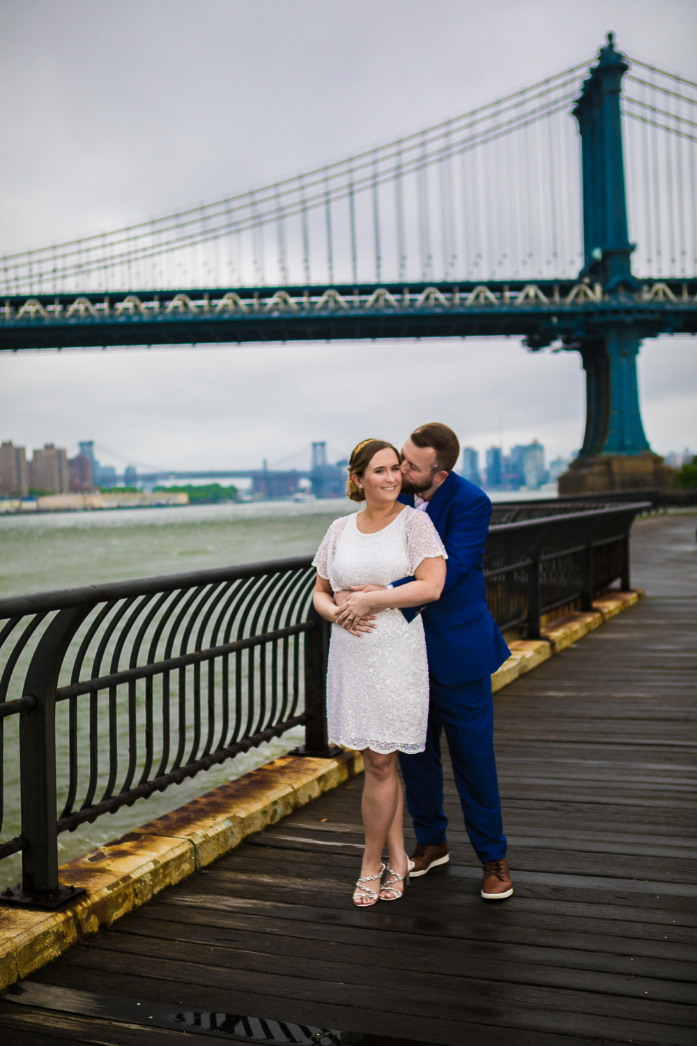 Bride and groom embracing. New York Bride in a short wedding dress and groom in a blue suit pose together for outdoor wedding photos in New York City. | Intimate Wedding at the Malthouse in Manhattan, New York City.