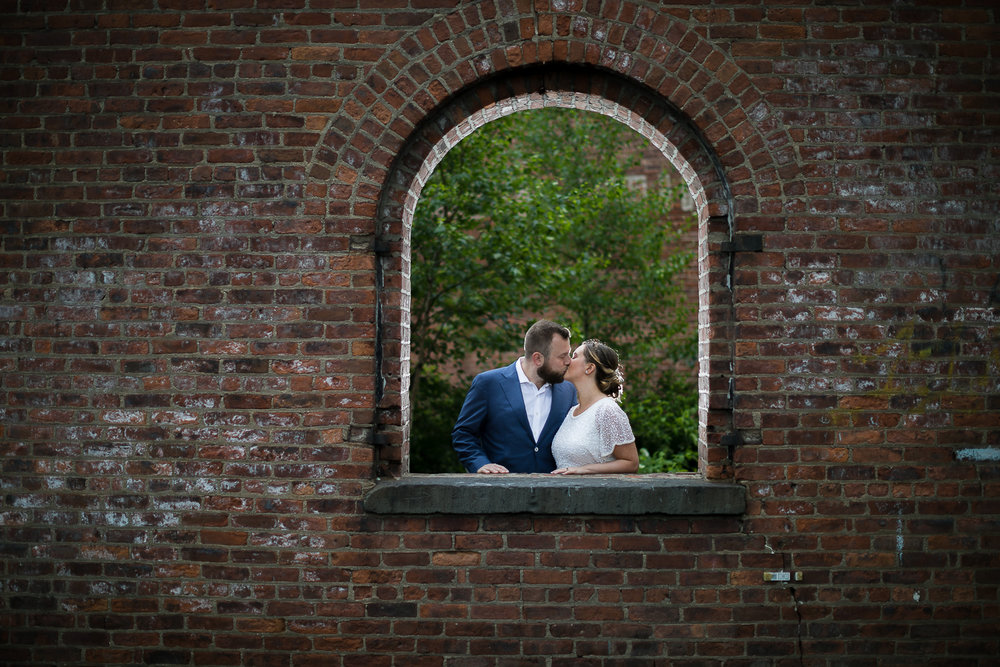 Bride and groom kissing against a brick wall. | Intimate Wedding at the Malthouse in Manhattan, New York City.