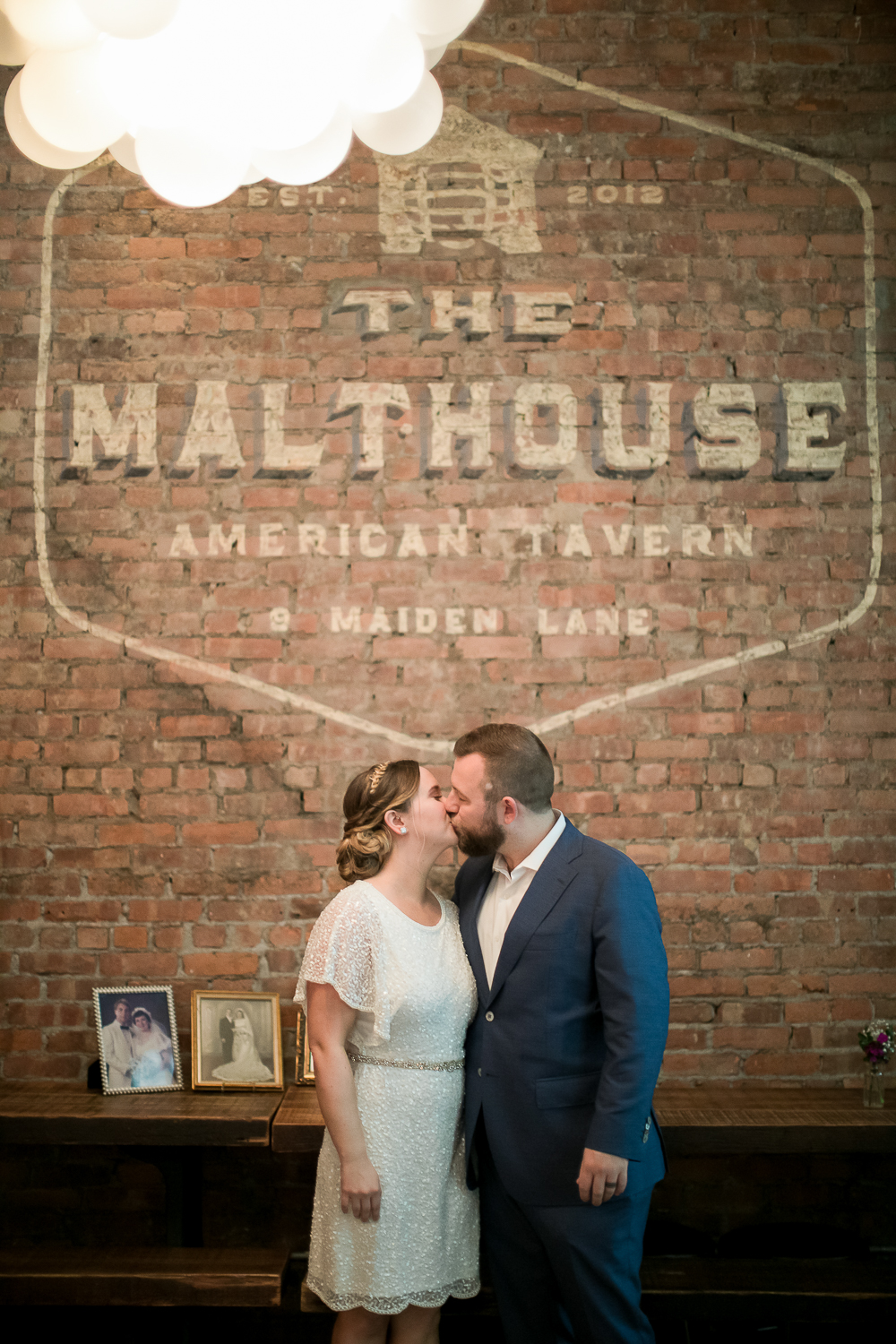 Bride and groom kissing in front of a brick wall at an Intimate Wedding at the Malthouse in Manhattan, New York City.