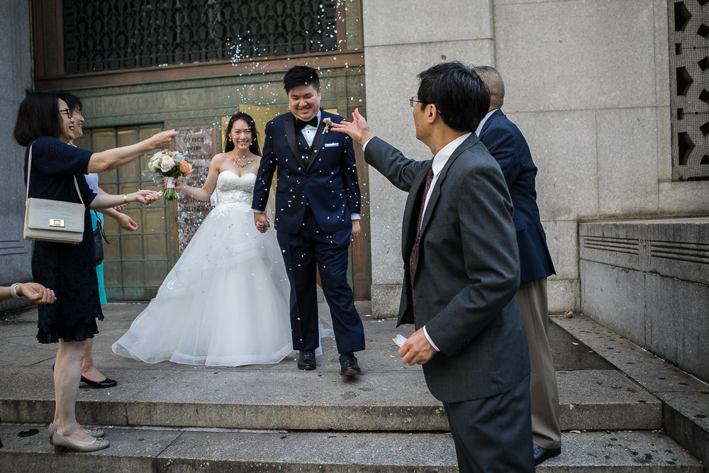 Wedding guests throwing confetti at the couple after getting married at City Hall NYC   New York City Hall Wedding Photographer   Jason and Susanna's Glam NYC Elopement
