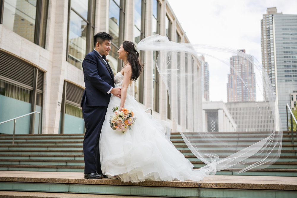Wind blowing a bride's veil while posing for wedding portraits at Lincoln Center in New York City  Lincoln Center Wedding Photos   Jason and Susanna's Glam NYC Elopement