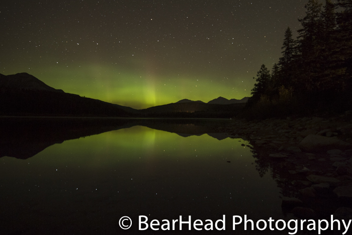 The northern lights and the big dipper are reflected into the lake.