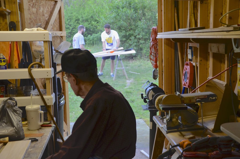 Granddad watching Corbin and I cut some wood from inside his shop.