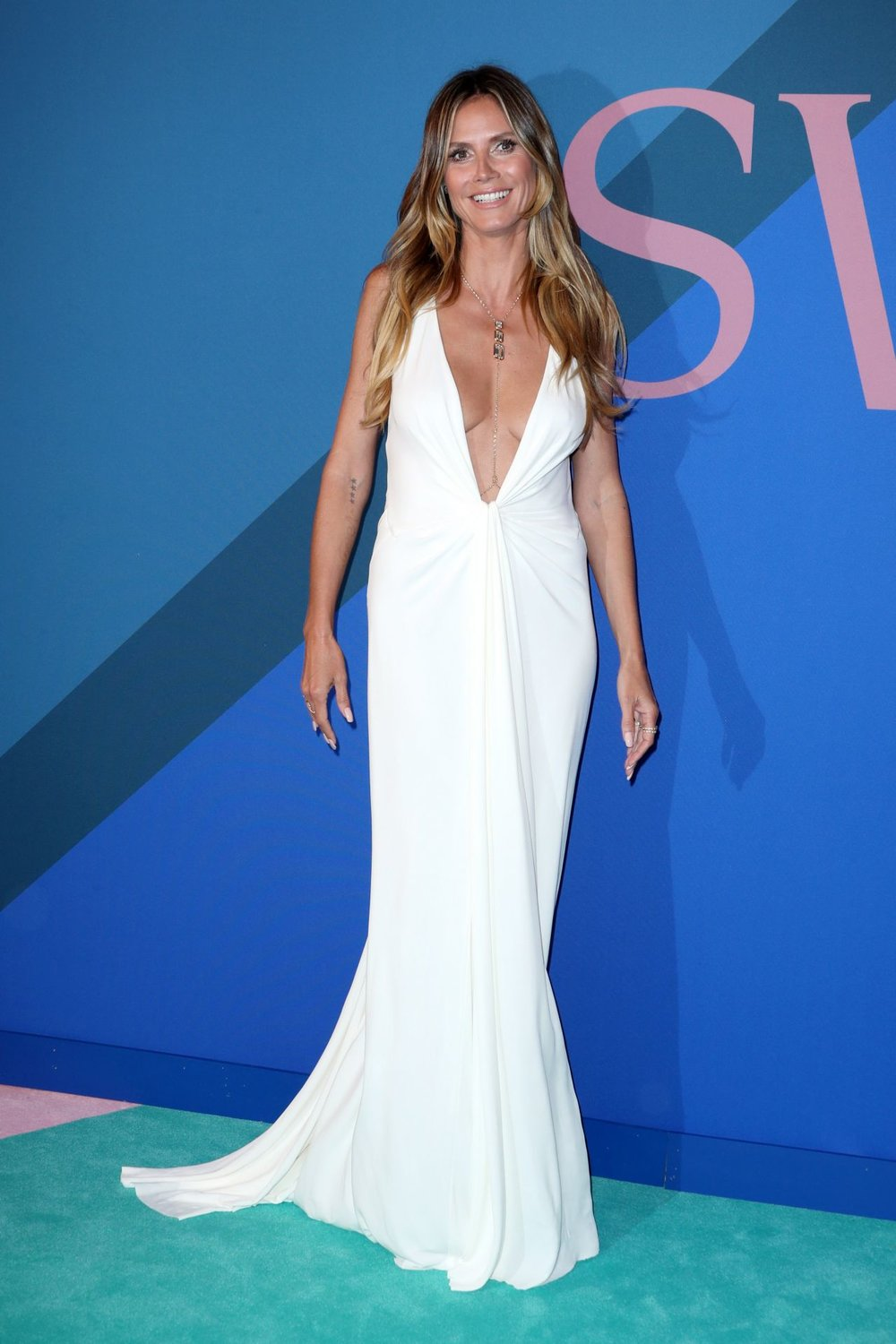 "Heidi Klum - This is also one of my favorite looks because it has a ""Greek Goddess"" vibe to it. The plunging neckline gives this simple white dress an unique twist."