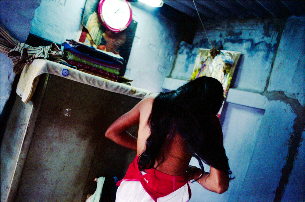"Rina, 28, became a prostitute after her manager at a cosmetics company pressured her for sex in exchange for a promotion. ""I have no past, my only identity is a sex worker."" Her mother is also a sex worker. Many people cite lack of empowerment for women as a major cause of HIV/AIDS in India."