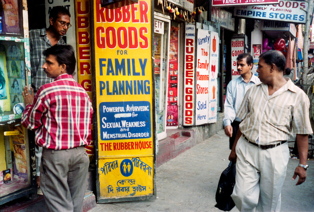 "A strip of ""rubber goods"" stores in Calcutta. Many people in India are embarrassed to buy condoms and have no knowledge of how to use them."