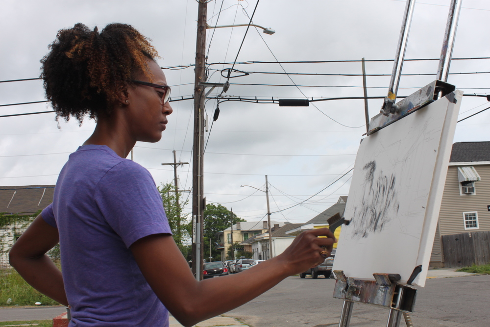 "Katrina Andry; Photography by H. Hickman  In May 2015, local artists Katrina Andry, Ron Bechet, Amy Bryant, Jer'Lisa Devezin, Keith Duncan, Horton Humble, and Varion Laurent engaged in a ""Live Action Painting"" of portraits of blighted houses. This quiet event unfurled without PR attention—it was a humble opportunity for artists to engage in dialogue with residents and meditate on the sensory experience of blight. The event took place soon after the City of New Orleans placed several hundred blighted properties up for auction; housing rights advocates and neighbors alike feared that the auction would lead to a land grab and bloodletting of rapidly gentrifying neighborhoods like New Orleans' historic 6th Ward. Residents reported non-local white folks ""swarming"" the neighborhood with cameras. Blights Out was interested in carefully navigating the delicate situation, strategically bringing only local Black artists to paint plein air and engage in candid conversation about the changing neighborhood. The decision to invite only Black artists was controversial amongst our participants and generated a meaningful discussion about race relations, gentrification, and public perception."