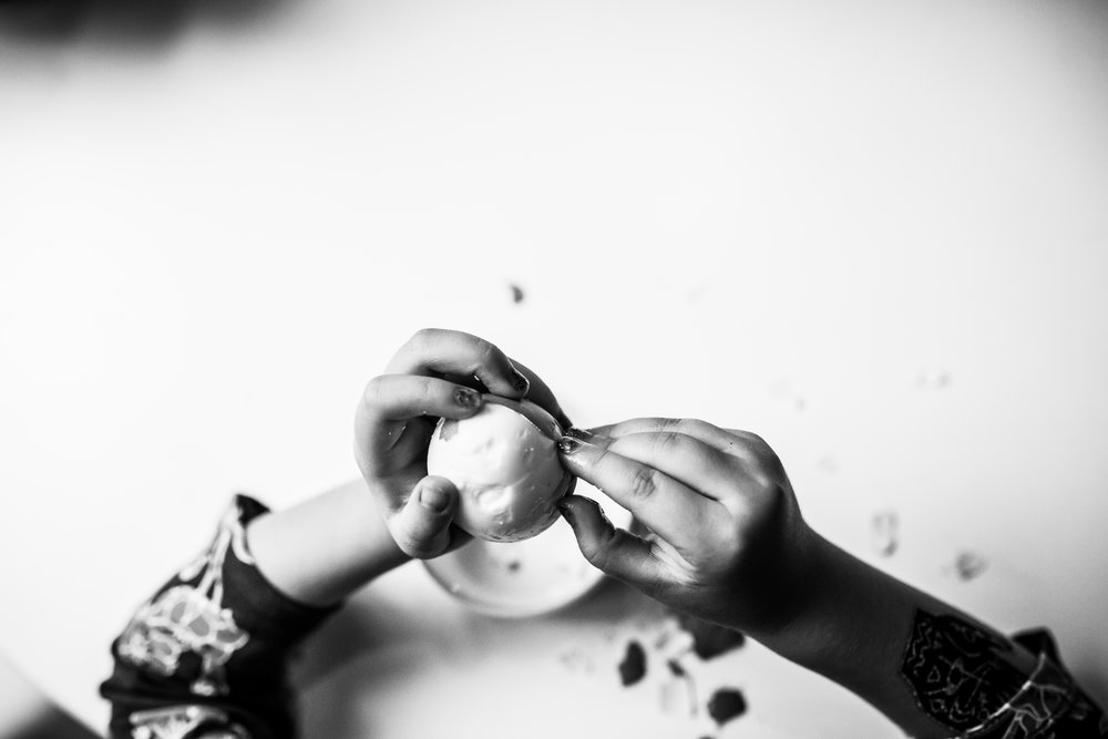 child peeling an egg