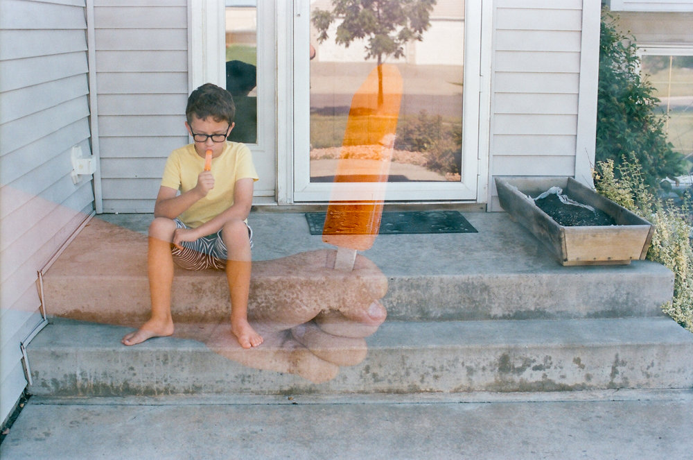 Boy and popsicle front step double exposure
