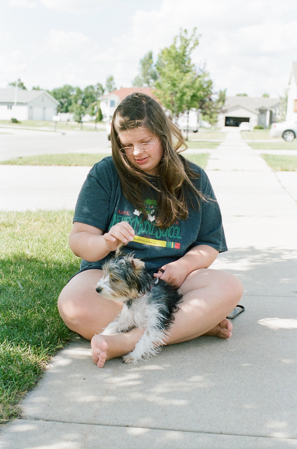 Teen and puppy on sidewalk
