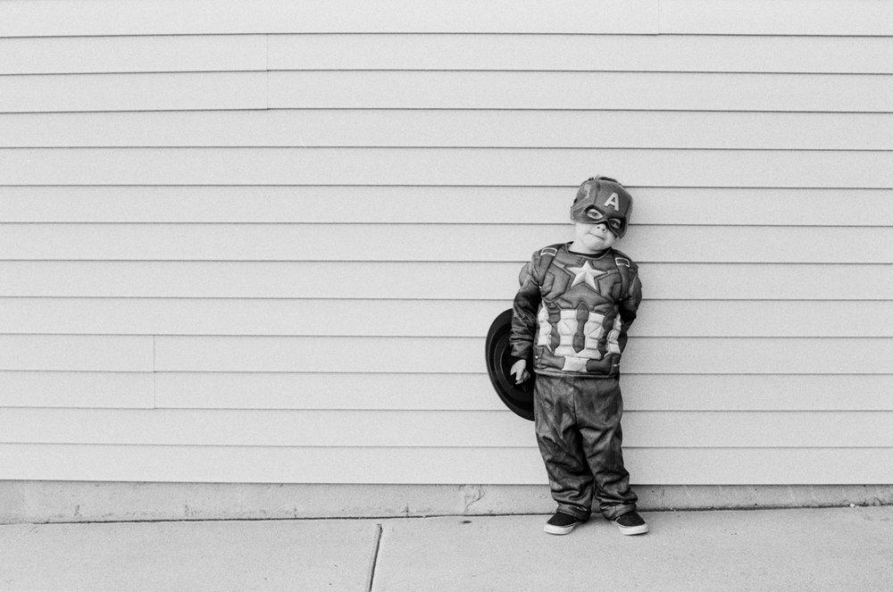Boy outside by garage on Halloween posing for a film portrait.