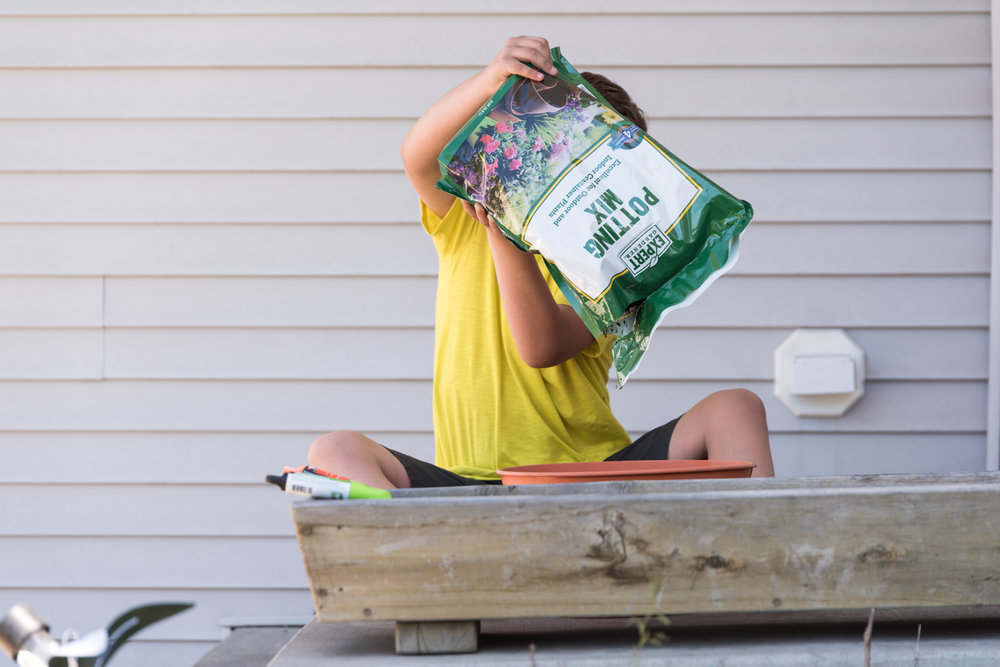 Boy dumping potting soil into a container in Fargo, ND.
