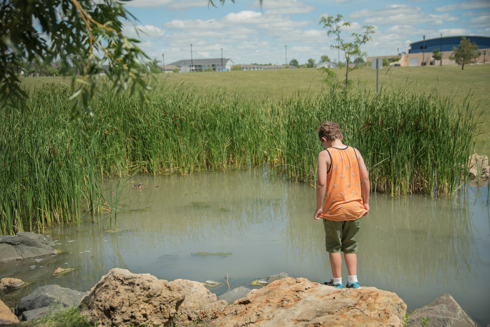 Boy-standing-pond-fargo-park