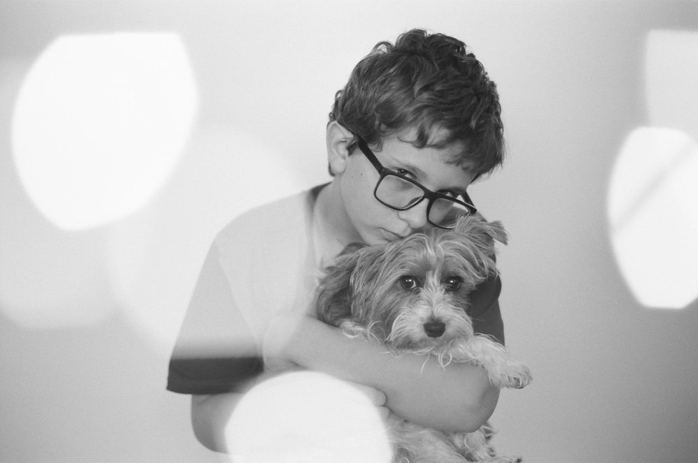 A young boy hugging his Yorkie puppy in a studio session Fargo.