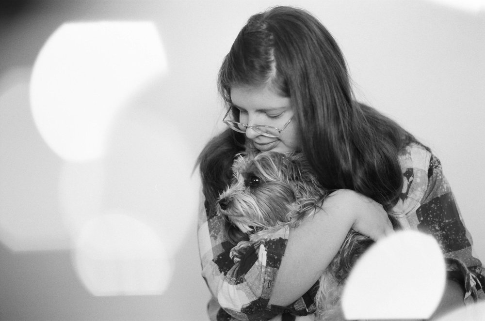 A teenage girl hugging her Yorkie puppy in a studio session Fargo.
