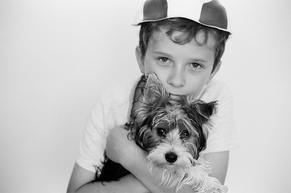 A boy hugging his yorkie dog and looking into the film camera.