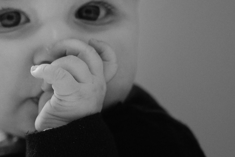 Detail shot of a six month old baby sucking her thumb.