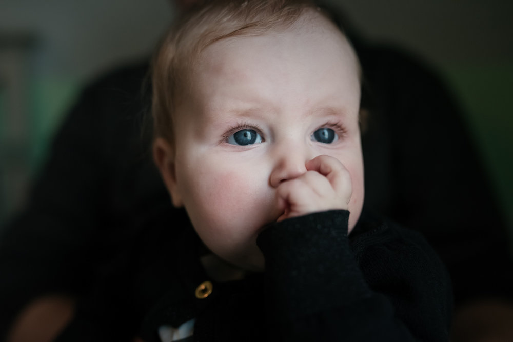 Baby sucking her thumb in window light.