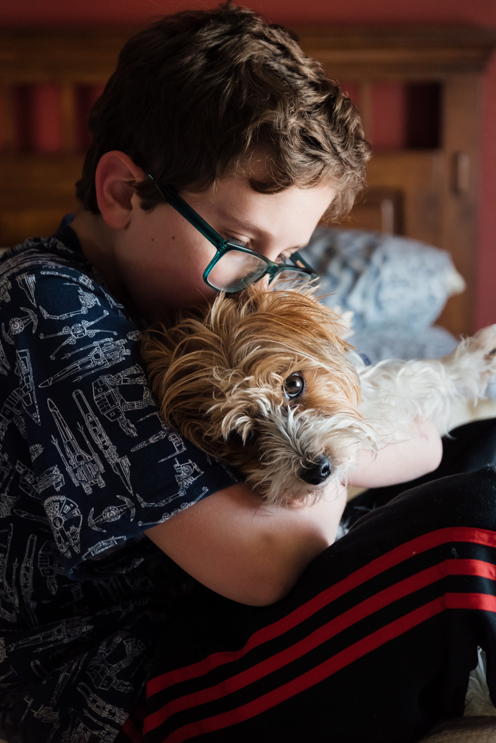Photo of boy hugging his dog in bedroom window light.