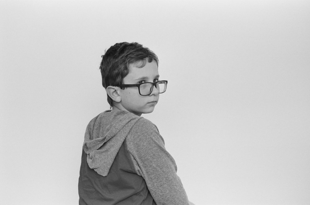 Portrait of a boy wearing glasses in black and white.