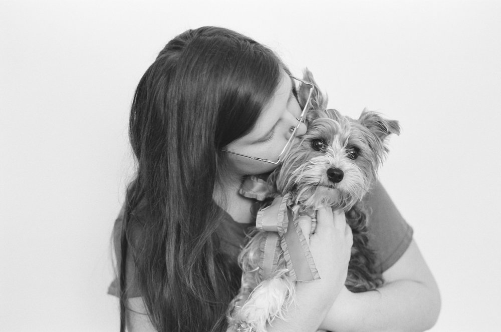 Portrait of a teen kissing her Yorkshire Terrier dog.