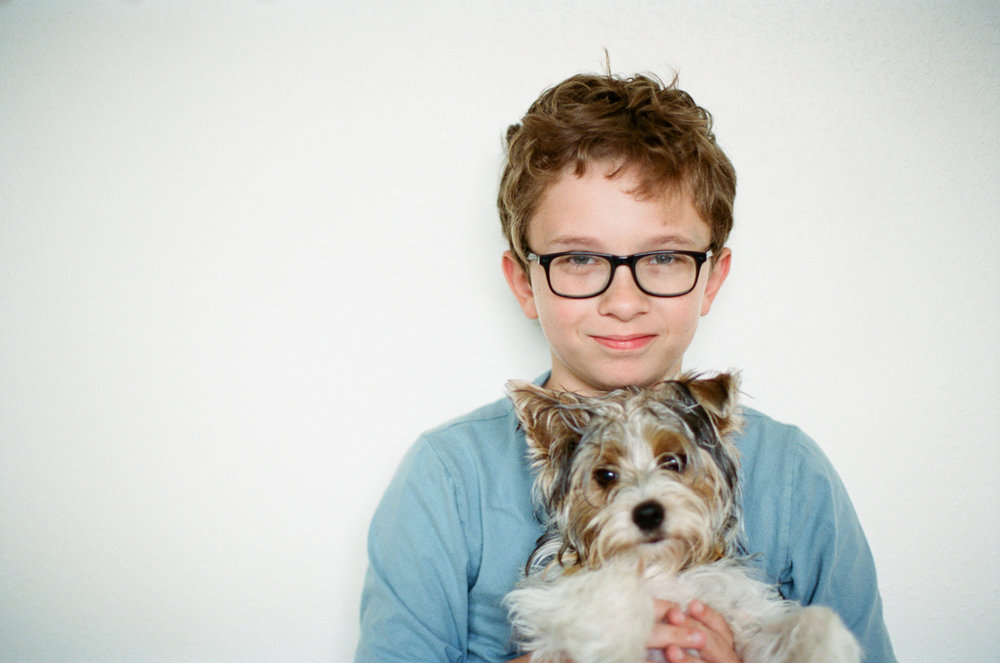 Portrait of a boy holding his Yorkshire Terrier dog.