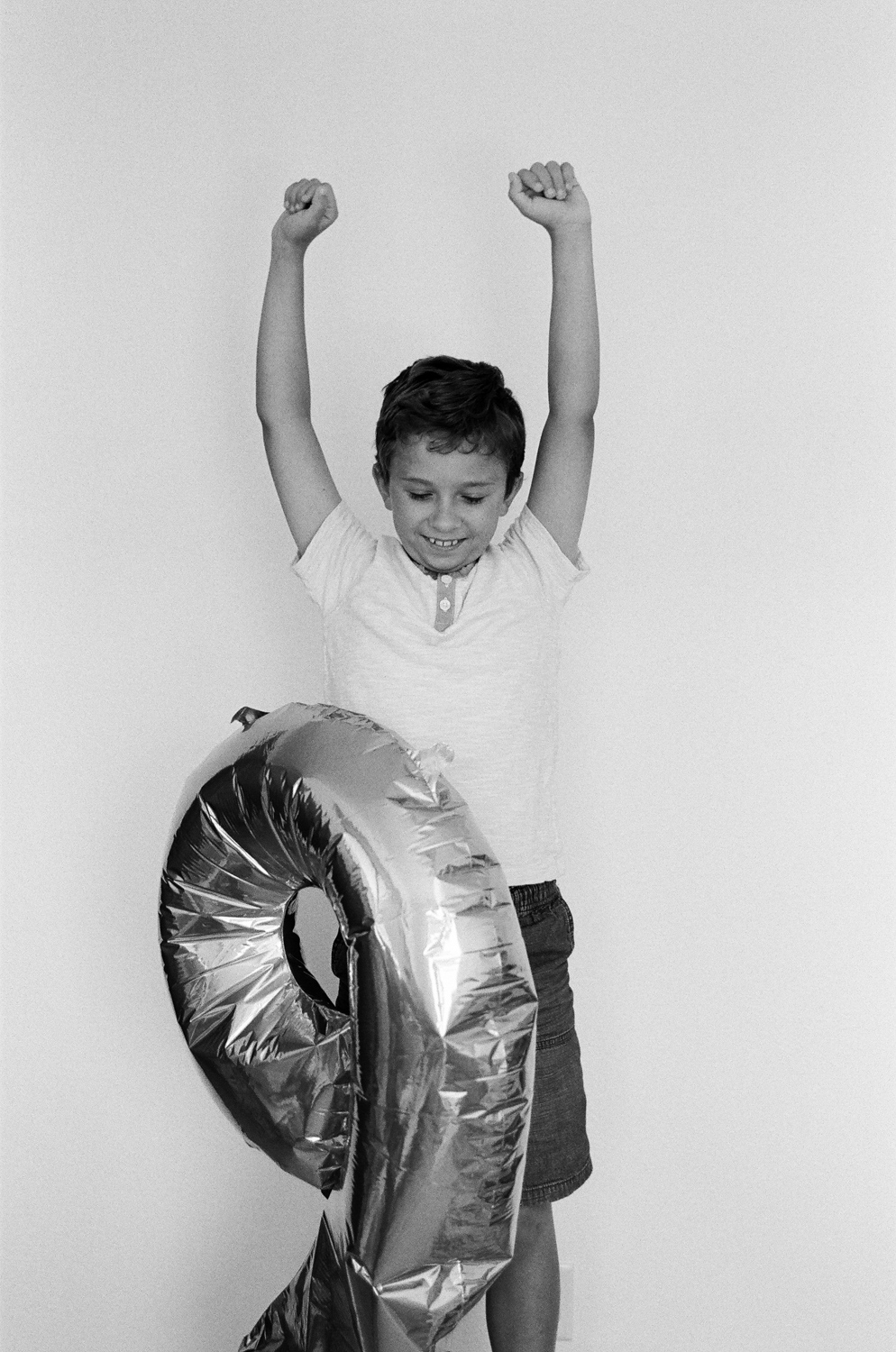 A young boy celebrating his birthday with a number balloon.