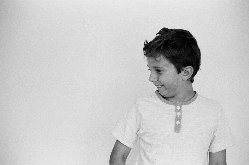 Profile portrait of a boy smiling and being silly.