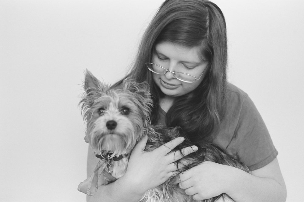Portrait of a girl holding her yorkie dog on her lap.