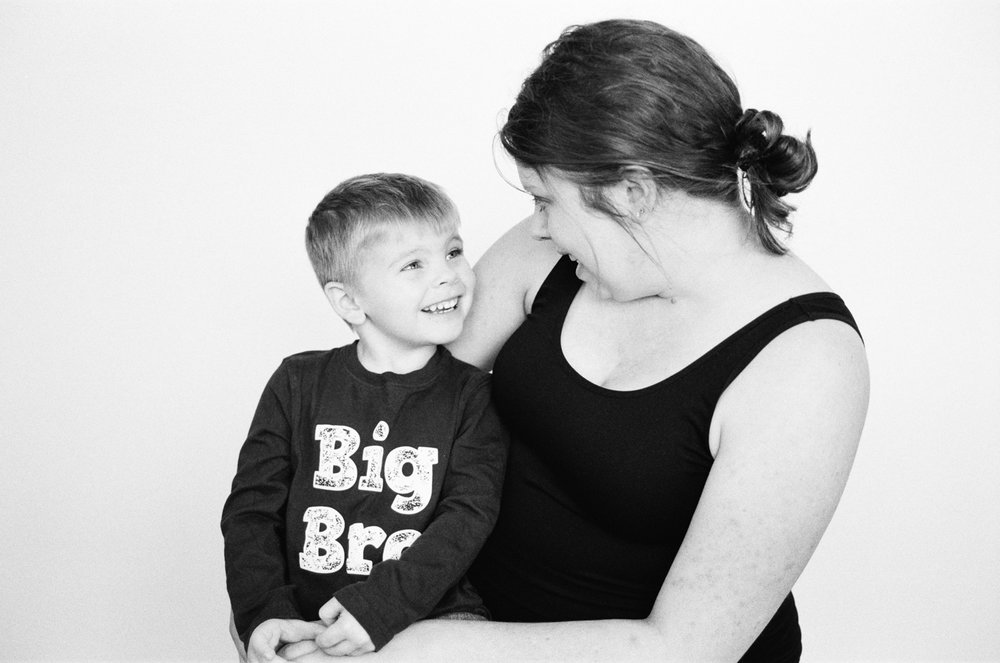 Boy with his mom taking a portrait to celebrate his becoming a big brother.