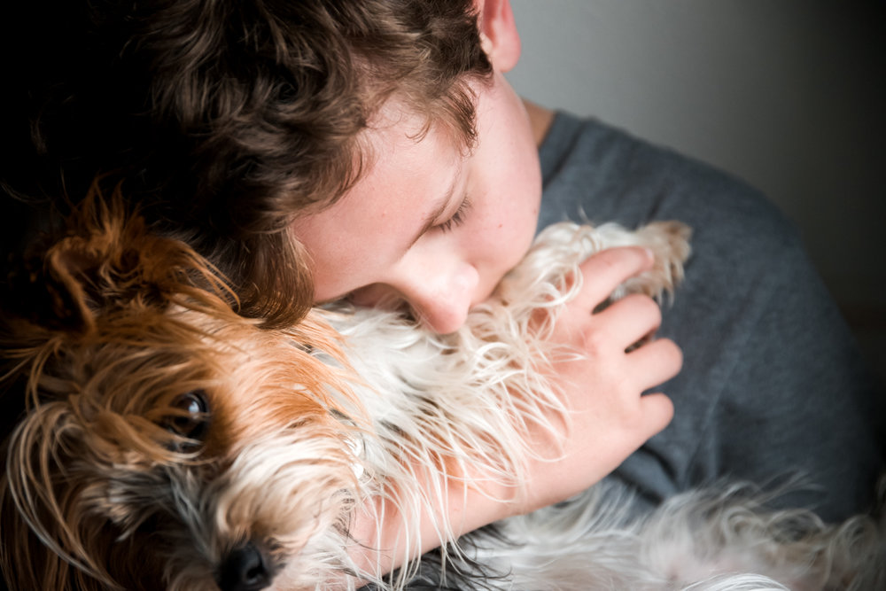 Boy hugging his Yorkie in kitchen, Fargo, ND.