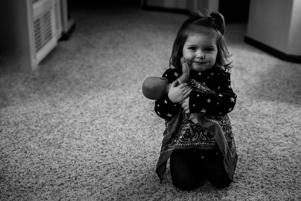 A little girl nurturing her baby doll at in home daycare in West Fargo.