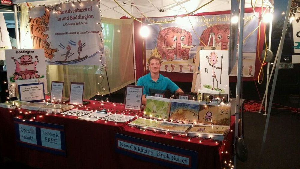 Author James Zwerneman shows off The Adventures of Ta and Boddington with Christmas lights at a local florida market.jpg