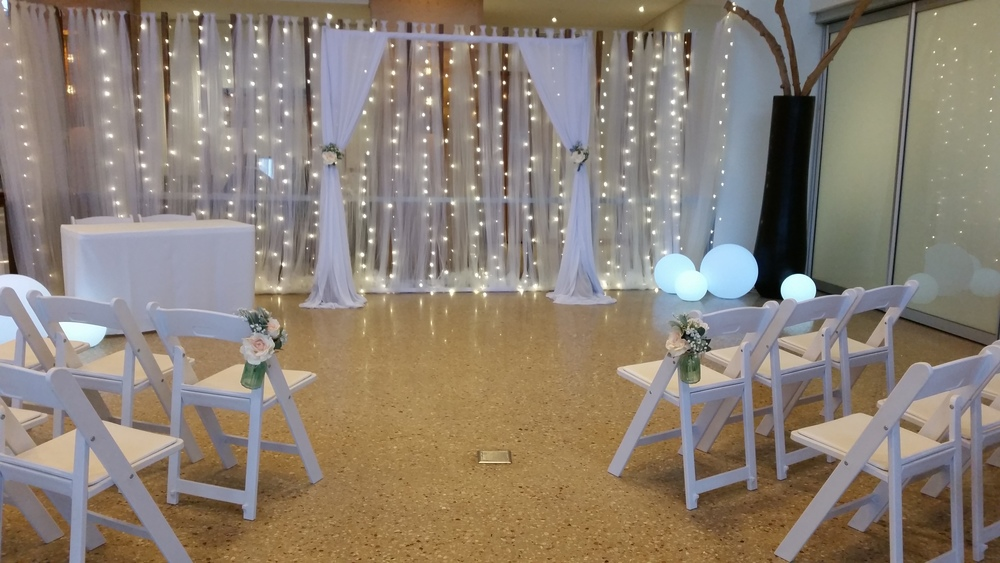 Arch With White Drapes, Tulle & Waterfall Fairy Lights, Led Balls & Gladiator Chairs